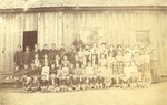 Group of Training School Students in Front of Wooden Building by unknown