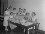 Group of Female Individuals with Stacks of Publications on Table 1 by Opal R. Lovett