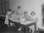 Group of Female Individuals with Stacks of Publications on Table 2 by Opal R. Lovett